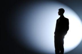Businessman silhouetted in a spotlight